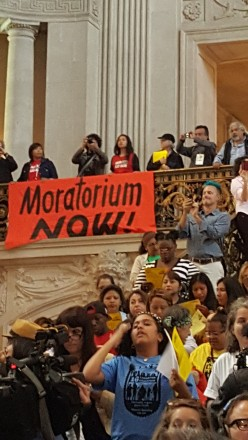 Housing activists in City Hall, with banner: Moratorium Now!