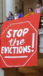 Housing activists unfurl banner at City Hall: Stop the Evictions!