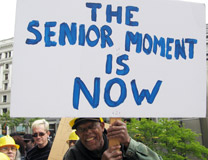 "Photo of SDA demonstration with placard reading ""The Senior Moment Is Now"""