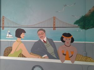 People in vintage clothing in a boat in front of the Golden Gate Bridge