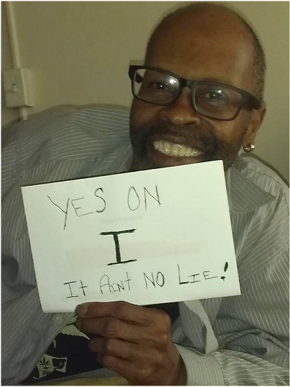 "Photo of SDA Member and Phone Canvasser Greg Ledbetter holding a sign saying: ""Yes on I – It Ain't No Lie!"""