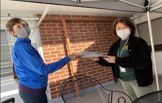 SDA Staffmember Sarah Jarmon (right) turns ballots in to Voter Registrar staff at an Oakland nursing facility.