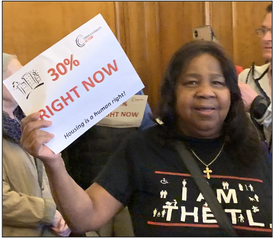 "Photo of a woman holding a sign that reads ""30 percent RIGHT NOW"""